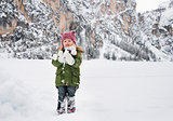 Happy child in green coat playing with snow
