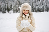 Woman looking on snow in hands while standing outdoors
