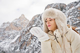 Woman in white coat and fur hat blowing snow from hand outdoors