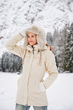 Woman in coat adjusting hat while standing in winter outdoors