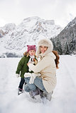 Mother and child playing outdoors in front of snowy mountains