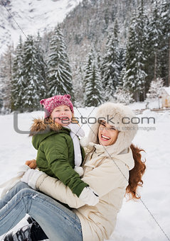 Portrait of smiling mother and child playing outdoors