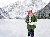 Happy child in green coat playing with snow outdoors