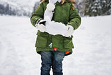 Closeup on snow in hands of child in green coat