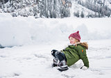 Happy child in green coat fell while playing in the snow.