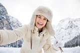 Woman in white coat and fur hat taking selfie in winter outdoors