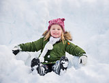 Happy child in green coat sitting on the snow