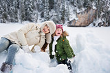 Portrait of mother and child playing with the snow outdoors