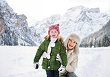 Smiling mother and child outdoors in front of snowy mountains