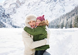 Mother and child hugging outdoors in front of snowy mountains