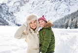 Happy mother and child outdoors in front of snowy mountains
