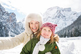 Mother and child taking selfie in front of snowy mountains