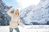 Happy woman in coat and fur hat throwing snow ball outdoors