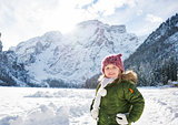 Happy child in green coat standing in front of snowy mountains