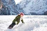 Child playing with the snow in the front of snowy mountains