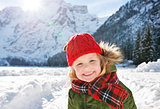 Smiling child standing in the front of snowy mountains