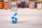 Blue white colored capsules in glass container