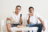 Men watching sport game on tv together