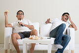 Men watching sport game on tv at home