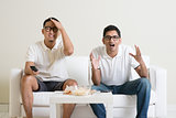 Men watching football match on tv at home