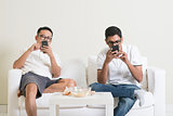 Bored friends playing own smartphones