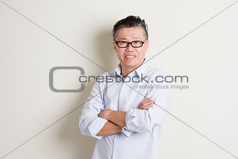Portrait of mature Asian male arms crossed