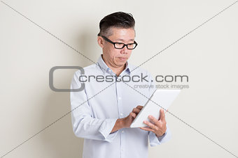 Portrait of mature Asian man using tablet pc