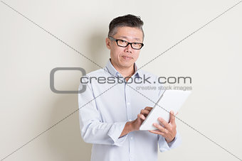 Portrait of mature Asian man using tablet computer