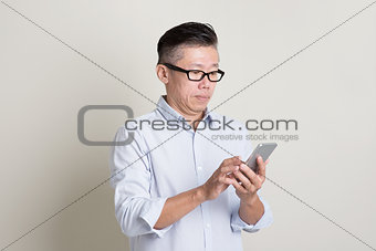 Portrait of mature Asian man using smartphone