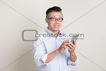 Portrait of mature Asian man using smart phone