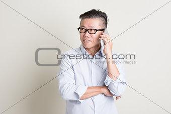 Mature Asian man talking on smartphone