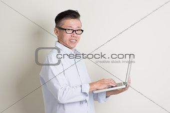 Mature Asian man using pc notebook