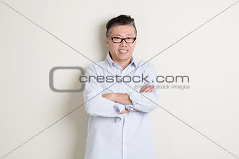 Portrait of mature Asian man arms crossed