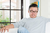 Mature Asian man sitting at home.