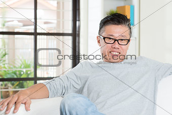 Mature Asian man sitting at home.