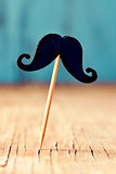 felt mustache in a stick on a wooden surface