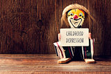 old marionette with a signboard with the text childhood depressi