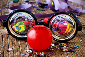 fake eyeglasses, red clown nose and confetti