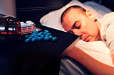 pills and young man laying face down in bed