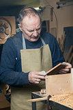 Men sandpaper grinds wood product in a workshop