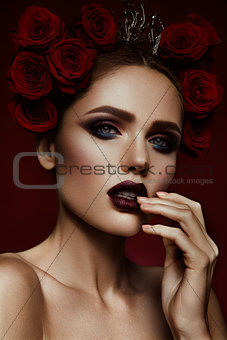 Beauty fashion model girl with dark makeup and roses in her hair