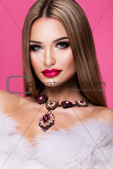 Beautiful young woman with long hair posing on pink shiny background.