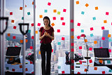 Busy Person Writing Many Sticky Notes On Large Window