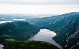 Inland fjord between steep cliffs against green landscape