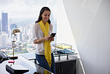 Business Woman Text Messaging On Phone In Office