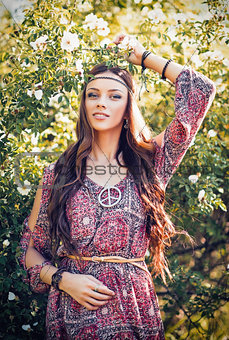 Portrait of beautiful young hippie girl among the flowers