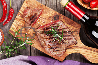 Grilled beef steak and red wine bottle