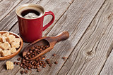 Coffee cup, beans and brown sugar on wooden table