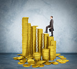 Businessman walking on stack of coins