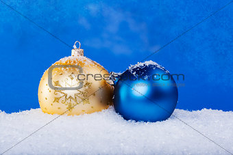 gold Christmas balls in the snow